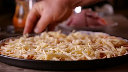 grated : Hand rotate a pizza sprinkled with cheese in baking pan - close-up, slow motion