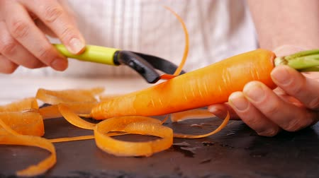 tábua de cortar : Woman hands peel fresh carrot with green leaves - close up, slow motion, camera slide