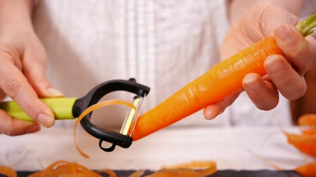 peeler : Woman hands peel fresh carrot with green leaves - close up, slow motion, camera tilt up