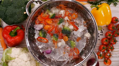 суп : Making a vegetable soup, ingredients falling into cooking pot filled with water - top view, slow motion