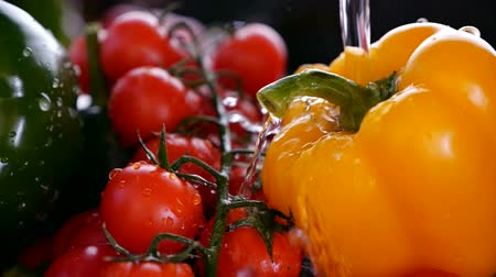 раковина : Water stream wash vegetables splashing off a bell pepper in a strainer - closeup, slow motion