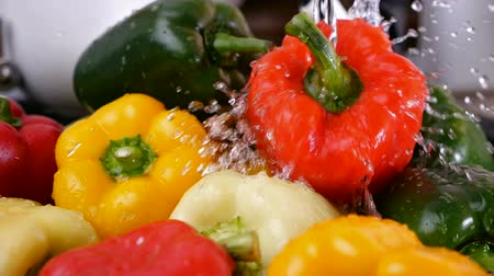 mosogató : Male hands start washing lots of delicious bell peppers at the kitchen sink - turning on the water, slow motion, camera slide Stock mozgókép