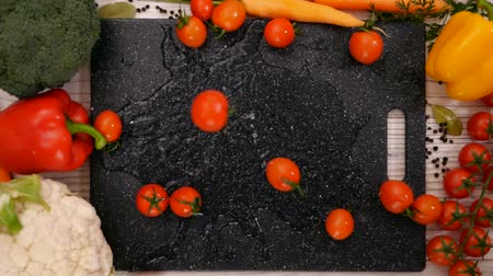 tomates cereja : Cherry tomato falling on chopping board framed by fresh vegetables on the table - slow motion, top view