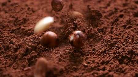 hazelnuts : Raisins, almonds and hazelnuts fall into cocoa powder stirring up clouds of the delicious chocolate ingredient - close up, slow motion, camera slide