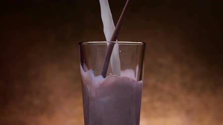 laktóz : Chocolate milk and milk streams pour into glass with the two flows blending and mixing, on dark background - close up, slow motion, static camera