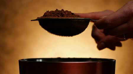kopogás : Woman knocking strainer with cocoa to sprinkle in bowl on golden background - macro close up, slow motion Stock mozgókép
