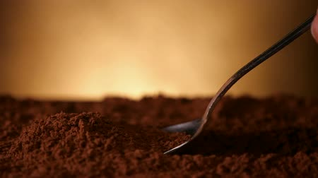 dose : Hand with spoon pushing through cocoa powder lifting up a spoonful - close up, slow motion, camera follow motion