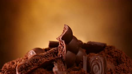 alimentos doces : Chocolate chunks heap and cocoa rotate on plate - close up, rotating on golden background Vídeos