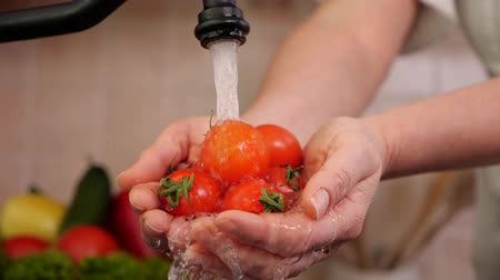 maréknyi : Woman hand washing handful of cherry tomatos at the kitchen sink - closeup, static camera, low angle view Stock mozgókép