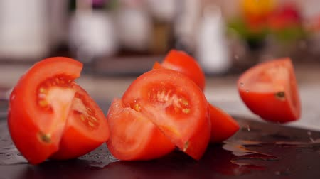 tábua de cortar : Tomato falling on chopping board breaking into slices on the table - slow motion, static camera Stock Footage