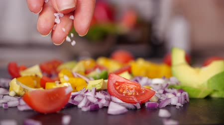 scatters : Woman hand adding large grain salt to vegetables mix prepared on the cutting board - closeup, slow motion of falling granules Stock Footage