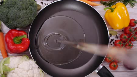 olejnatý : Cooking oil pouring into fry pan surrounded by fresh vegetables on the table - top view, slow motion Dostupné videozáznamy