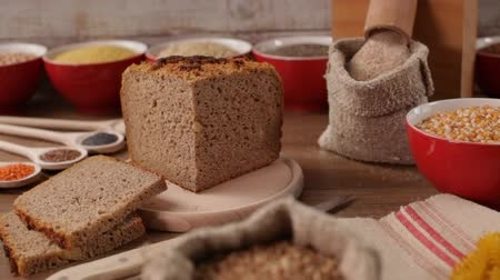 spoons : Making traditional wholemeal bread with fresh ground whole grain flour coming from a tabletop mill. Variety of seeds and grains base fro a healthy diet, camera slide. Stock Footage