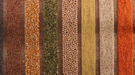 balanced : Various seeds and grains arranged in colorful stripes on the table - top view, gluten free and diverse diet concept, slow camera slide