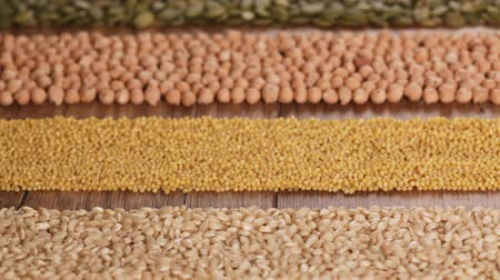 kasza jaglana : Various seeds and grains arranged in colorful horizontal stripes on the table - top view, gluten free and diverse diet concept, camera slide above
