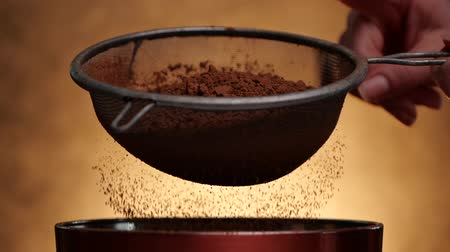 окропляет : Woman hand tap strainer to sprinkle cocoa - close up, slow motion, golden background
