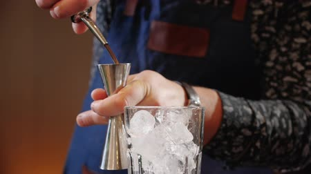 zavřít : Bartender hands pouring cocktail ingredients in measuring cup or jigger then on the ice cubes in a glass - close up, slow motion Dostupné videozáznamy