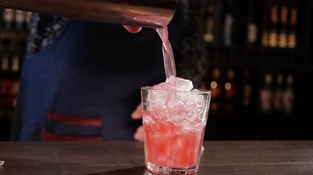 шейкер : Bartender hands pouring the mix from a shaker cup onto ice cubes in a glass - close up, slow motion of making a cocktail