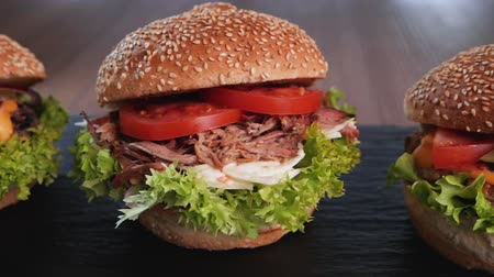навынос : Three hamburger variety - appetizing beef, pulled pork and chicken sandwich in a row with delicious ingredients - camera slide in a circle