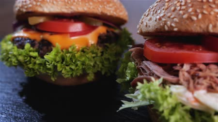 cheese slices : Appetizing hamburger variety - beef, pulled pork and chicken sandwich in a row, with delicious ingredients - slide in and out of frame diagonally Stock Footage