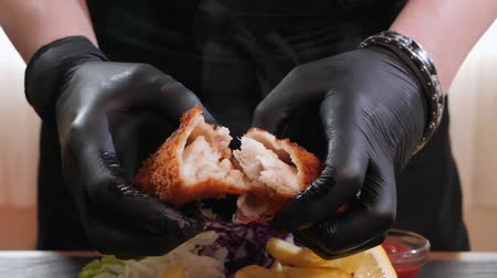 shred : Fried fish fast food menu with delicious meat served along appetizing french fries, cabbage garnish and sauce. Chef hands splits the fried fillet letting the steam rise. Camera zoom in.