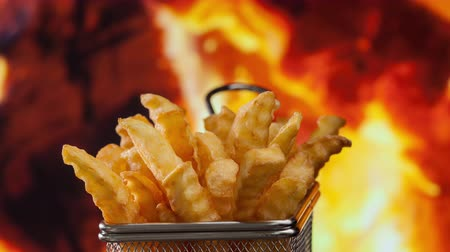 consumir : Delicious french fries slowly rotating in front of fire flames served in a metallic mesh frying basket shaped recipient
