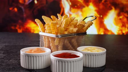 фасонный : French fries in front of fire flames served in a metallic mesh frying basket shaped recipient - camera slide