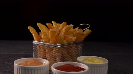 фасонный : French fries served in a metallic mesh frying basket shaped recipient with three sauce variety - dark background, camera slide parallax
