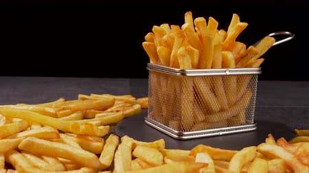 calorias : French fries served in a metallic mesh frying basket shaped recipient on slate plate - dark background, camera slide parallax and slowly tilt up Stock Footage