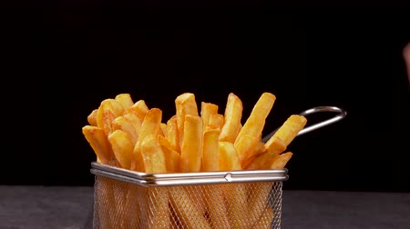recipient : Hands sharing delicious french fries served in a frying basket shaped recipient - dark background, camera slide