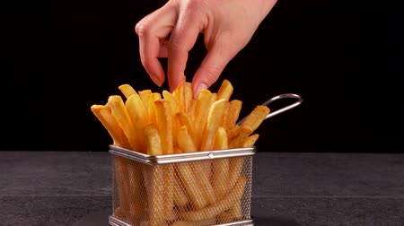 recipient : Hands sharing delicious french fries served in a frying basket shaped recipient - dark background, camera slide forward zooming in