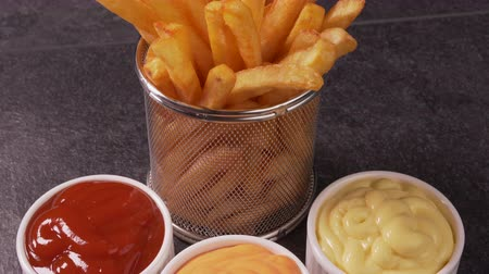 aanpak : Delicious french fries served in a frying basket shaped recipient with sauce variety - camera slide forward zooming in on the potato straws, tilting down Stockvideo