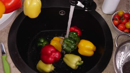 rinse : Lots of colorful bell peppers fall into kitchen sink - under the running tap water, slow motion, top view
