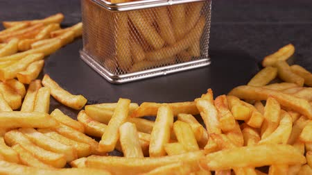 recipient : French fries served in a frying basket shaped recipient, hands taking pieces  - dark background, camera slide forward approaching and slowly tilt up Stock Footage