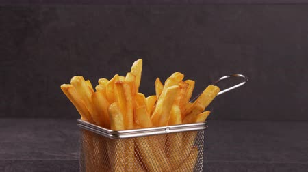 hranolky : Hands sharing delicious french fries served in a frying basket shaped recipient - gray background, camera slide forward zooming in