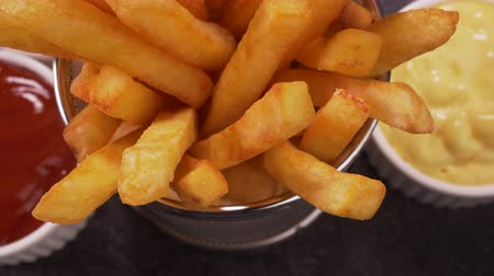 recipient : Hands taking delicious french fries served in a frying basket shaped recipient - camera pull back, zooming out
