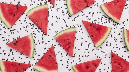 melão : Watermelon slices swinging among melon seeds. Fruit background. Top view, stop motion animation.
