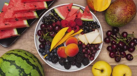 agrest : Summer fruits plate rotate and slowly empties. Top view, stop motion animation.