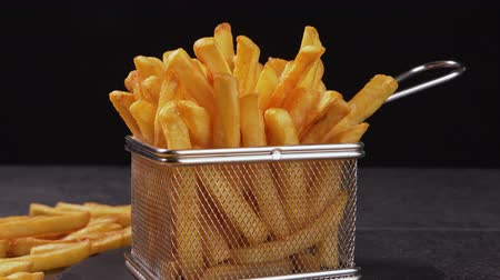 recipient : French fries served in a frying basket shaped recipient  - dark background, camera slide and slowly tilt up Stock Footage