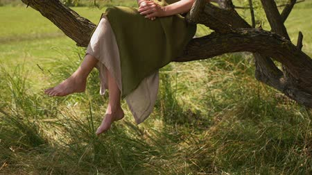 crossed : Woman relaxing outdoors in summer time enjoying some quiet time in nature - sitting on a tree branch
