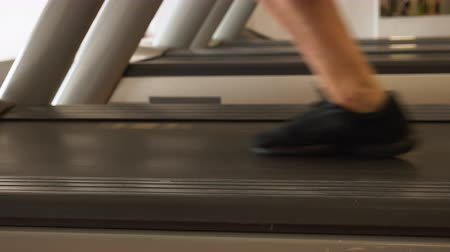 Feet running on treadmill - closeup, sliding camera