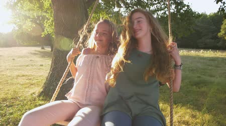 Two happy girls have fun smiling and swinging on rope swing outdoors - front view, slow motion