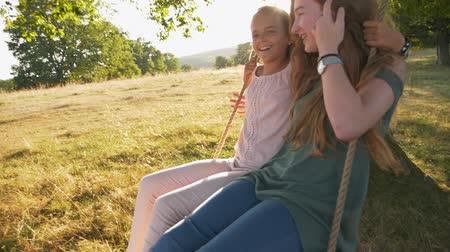 Two happy girls have fun smiling and swinging on rope swing and playing tricks on each other, outdoors - slow motion Stok Video