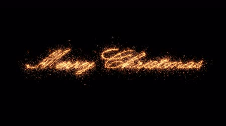 Sparkler text merry christmas appear written in sparkling twinkles and glitter on black background. Holiday themed  animation for any festive composition design. Stok Video