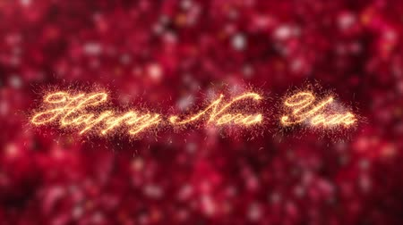 Happy new year calligraphy writing in sparkler twinkles appear over red xmas garland decorations background - rack focus to text Stok Video