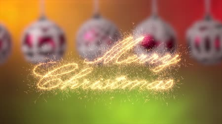 Merry christmas calligraphy writing greeting appear written in sparklers casting glittering particles. Sliding in front of beautiful christmas baubles hanging against smooth and warm lights background