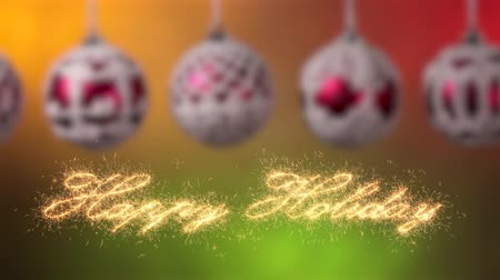 Happy holidays calligraphy writing greeting appear written in sparklers casting glittering particles. Sliding in front of beautiful christmas baubles hanging against smooth lights background