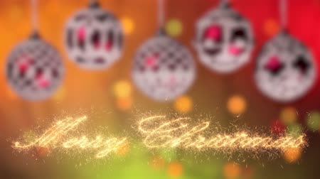Merry christmas greeting text appear written in sparklers casting glittering particles. Beautiful christmas baubles hanging uneven against blurry lights background Stok Video
