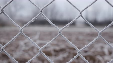 Metallic wire fence with hoarfrost on barren cold winter landscape - camera slowly slide