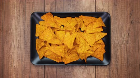 Tortilla chips filling then disappearing from a rectangular plate leaving a large black copy space - stop motion animation